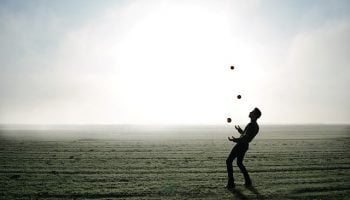 man jongleert in open veld