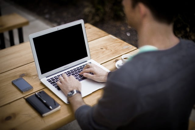 man werkt achter laptop