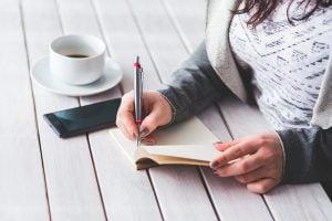 Vrouw zit aan tafel en maakt aantekeningen in een notitieboekje
