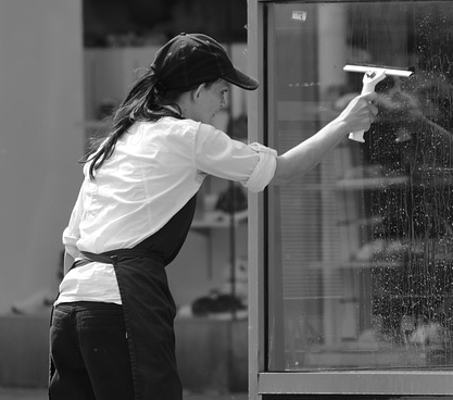vrouw zeemt ramen buiten