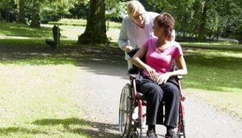 vrouw in rolstoel met vrouwelijke begeleider in contact met elkaar