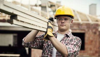 jonge bouwvakker draagt hout