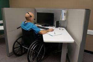 man in rolstoel werkt achter computer