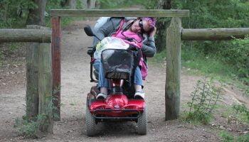vrouw in scootmobiel bukt voor obstakel op de weg