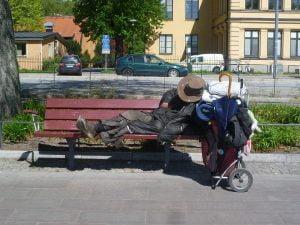 dakloze man slaapt op een bankje in een woonwijk