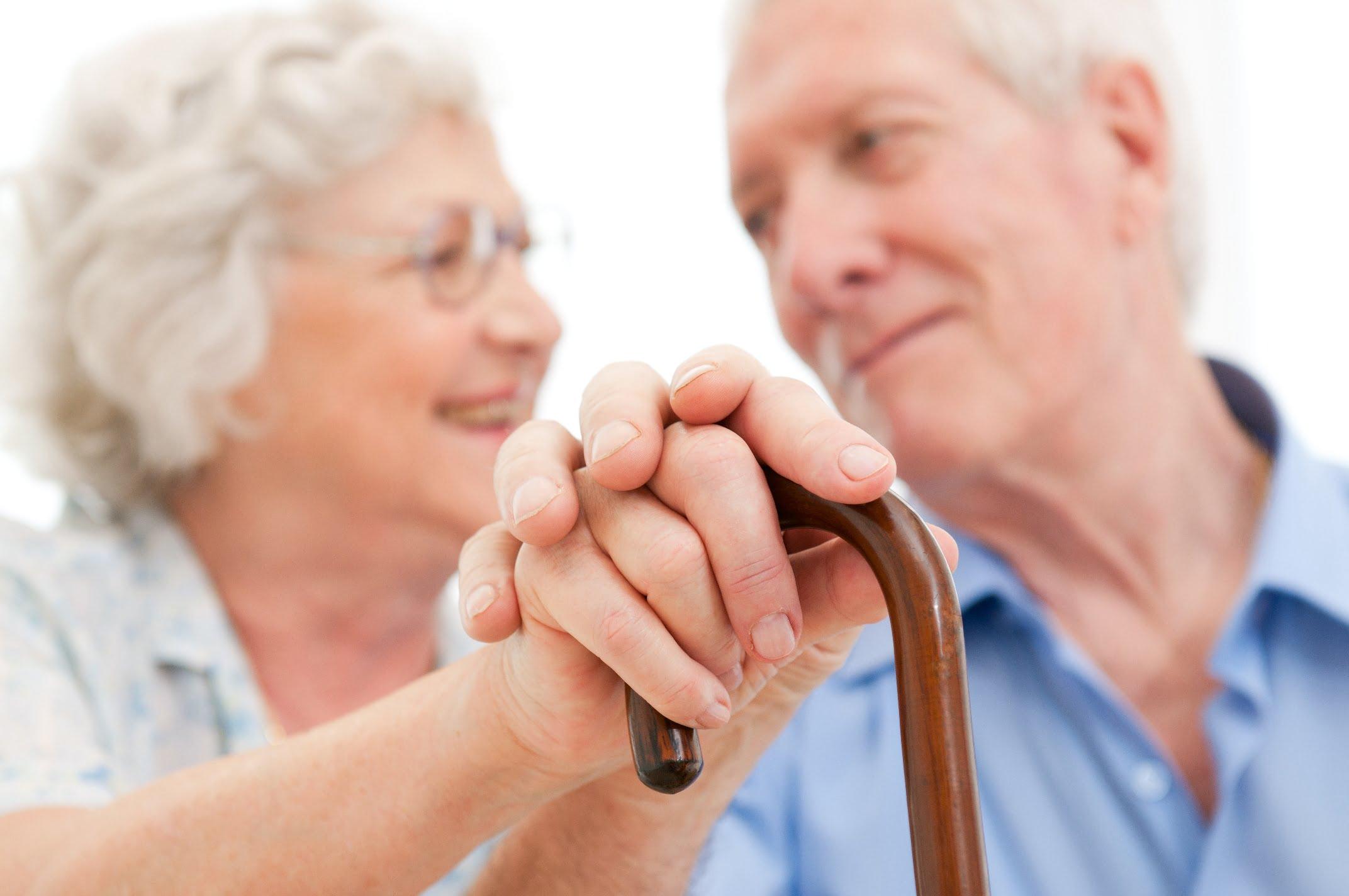 2 oude mensen kijken naar elkaar en steunen op wandelstok