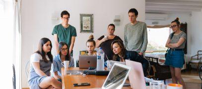 jongeren om een tafel met laptops