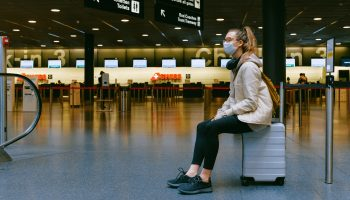 Vrouw zit op koffer met mondkapje