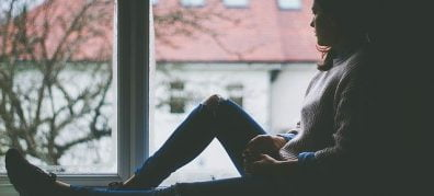 Meisje in vensterbank kijkt naar buiten